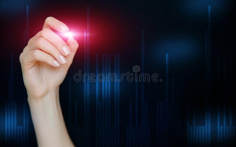 Kvinnlig hand som drar abstrakta finansiella diagram på oskarp blå mörk bakgrund Stearinljus forexdiagram royaltyfria bilder
