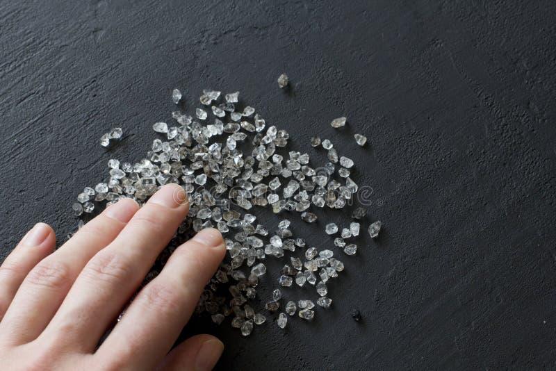 Kvinnlig hand som n?r f?r diamanter Naturliga stenar, spridning av stenar, kristaller kopiera avst?nd f?r din text arkivfoton