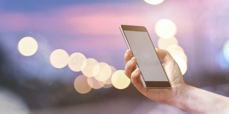Kvinnlig hand som rymmer den mobila smarta telefonen över ljus bokeh royaltyfria bilder