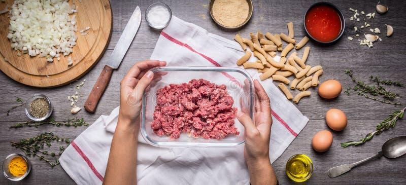 Kvinnlig hand som rymmer en bunke med köttfärs på det lantliga köksbordet, runt om lögningredienser för en smaklig matlagningpast royaltyfri bild