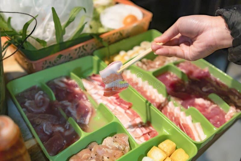 Kvinnlig hand som rymmer en skiva av griskött vid pinnen i den thailändska grillfestmenyn Moo Kra ta royaltyfri bild