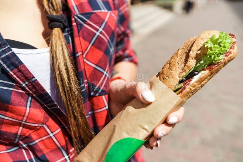 Kvinnlig hand som rymmer en smörgås royaltyfri foto