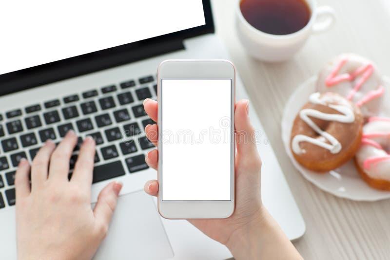 Kvinnlig hand som rymmer en telefon med skärmen och bärbara datorn arkivbilder