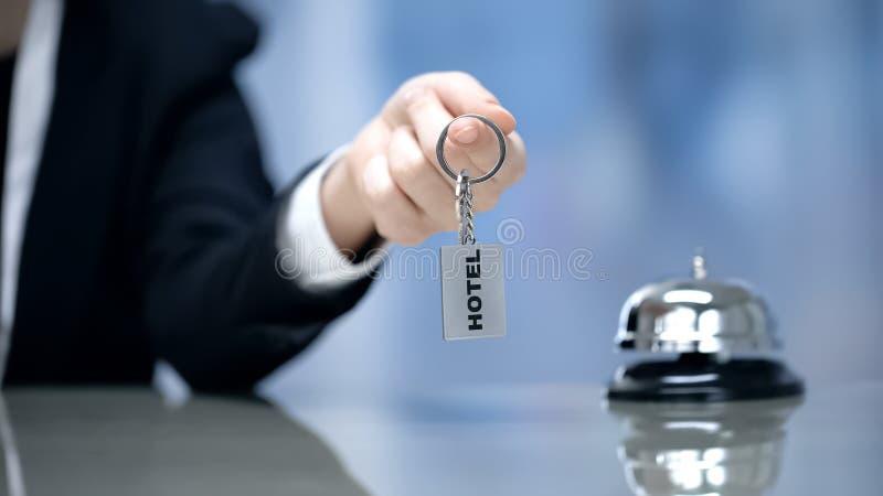 Kvinnlig hand som rymmer hotellrumtangenter nära klocka på mottagande, gästfrihetservice royaltyfria bilder