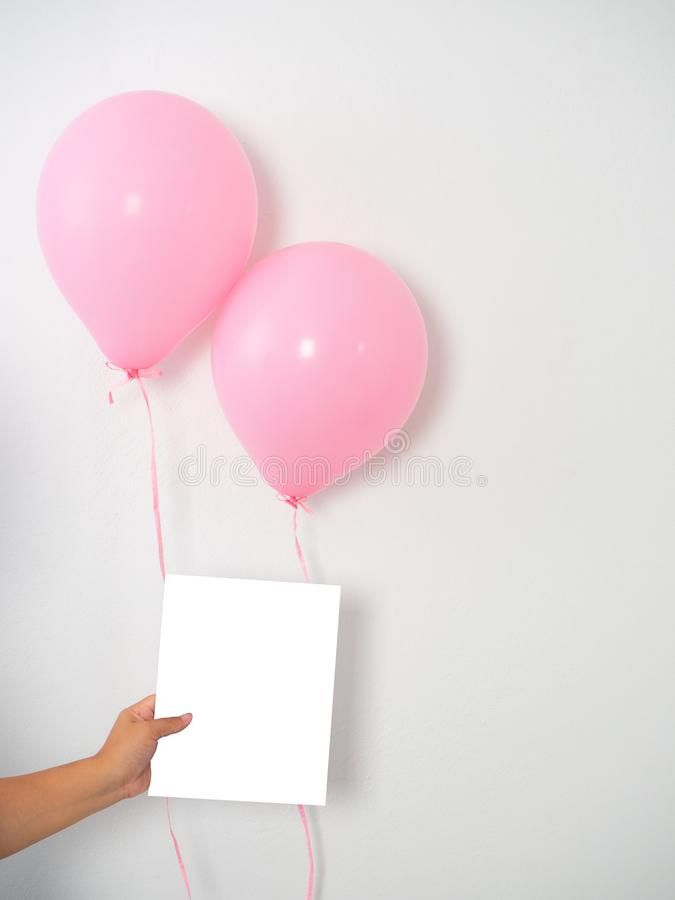 Kvinnlig hand som rymmer rosa ballonger fotografering för bildbyråer