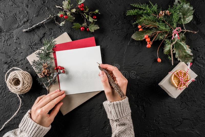 Kvinnlig hand som skrivar ett brev till jultomten på mörk bakgrund med jul gåva, bär, granfilialer, skein av jute xmas royaltyfria bilder