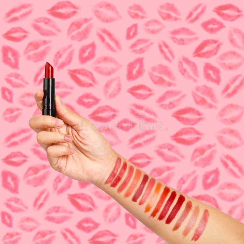 Kvinnlig hand som testar olika läppstift som visar provkartor arkivbilder