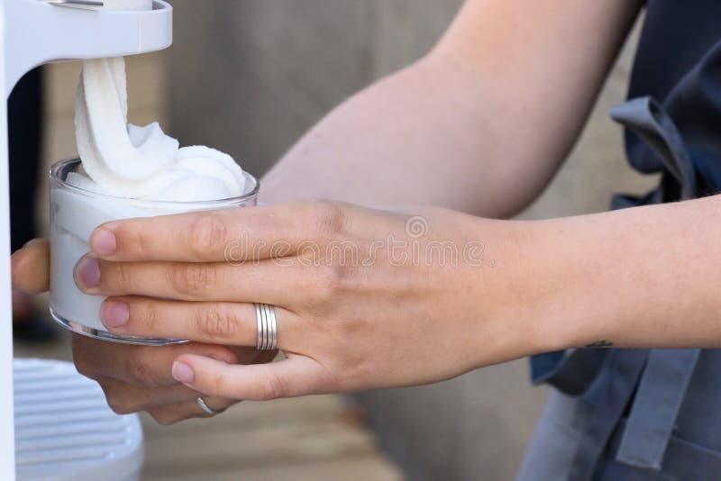 Kvinnlig hand som tjänar som mjuk glass från en maskin royaltyfri fotografi