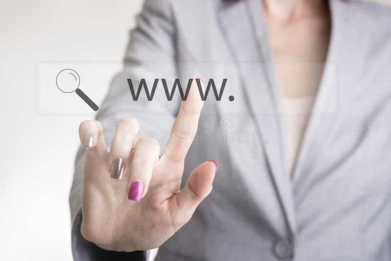 Kvinnlig hand som trycker på en rengöringsduksökandestång med www och förstorar gl royaltyfria foton