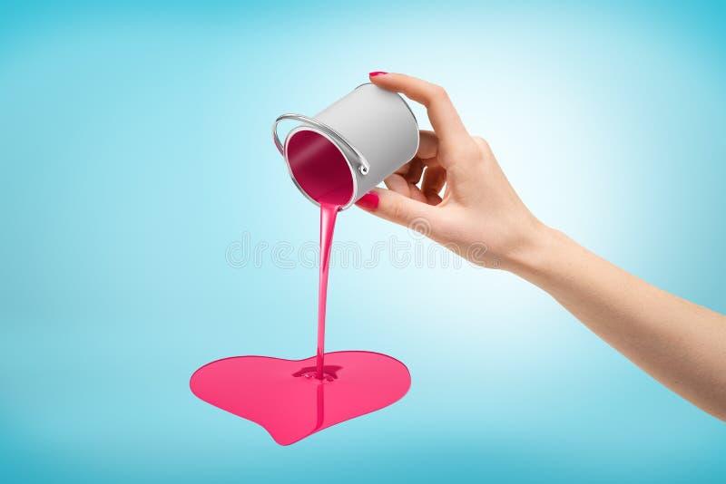Kvinnlig hand som vänder den lilla silvermålarfärghinken uppochnervänd med rosa hjärta format hälla på blå bakgrund arkivbild