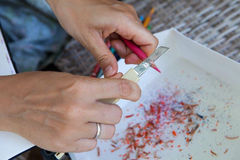 Kvinnlig hand vässade färgade blyertspennor arkivbilder