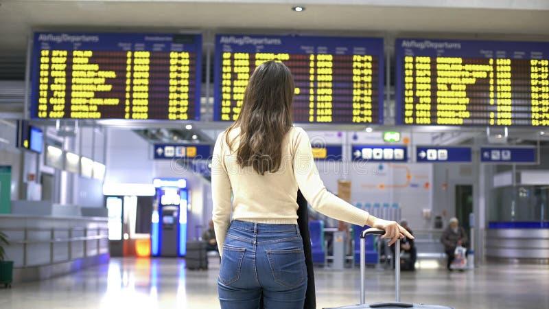 Kvinnlig handelsresande som ser information om avvikelseincheckning i flygplats, tur royaltyfria bilder