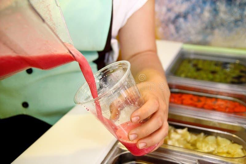 Kvinnlig handfruktsmoothie in i exponeringsglas Tjänad som nytt gjord fruktsmoothie i plast- kopp med sugrör fotografering för bildbyråer