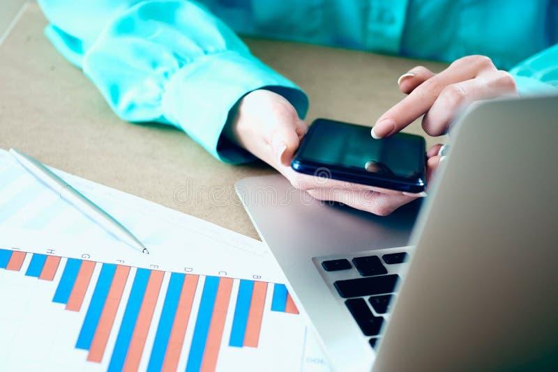 Kvinnlig handhållsmartphone som pekar fingerpekskärmtelefonen, finansiella grafer för bärbar dator på bakgrund fotografering för bildbyråer