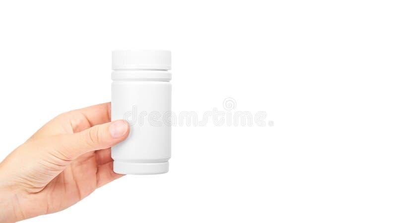 Kvinnlig handinnehavflaska med preventivpillerar bakgrund isolerad white kopieringsutrymme, mall royaltyfria bilder