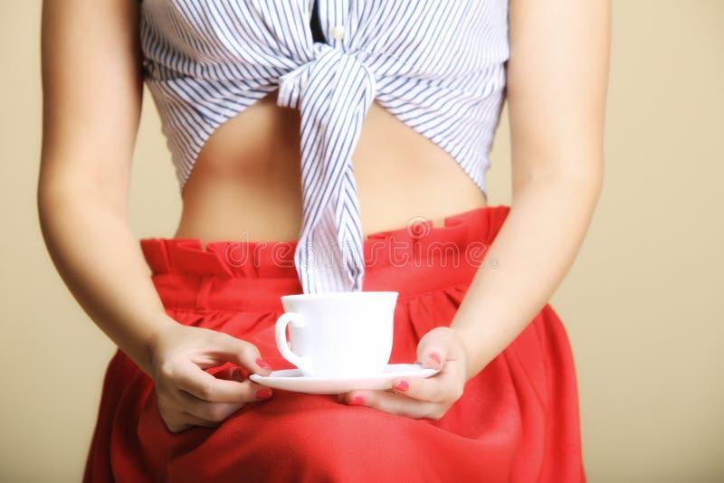 Kvinnlig handinnehavkopp av den varma drycken arkivfoto