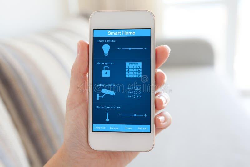 Kvinnlig handinnehavtelefon med det smarta hemmet på skärmen arkivbild