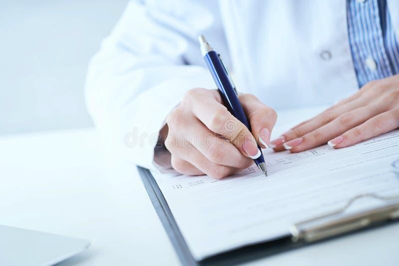 Kvinnlig handstil f?r penna f?r silver f?r innehav f?r medicindoktorshand n?got p? skrivplattacloseupen Lott av skrivbordsarbete  royaltyfri bild