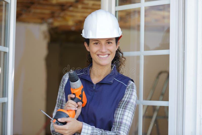 Kvinnlig handtool för byggnadsarbetareinnehavskruvmejsel och sladdlös skruvmejsel arkivfoto