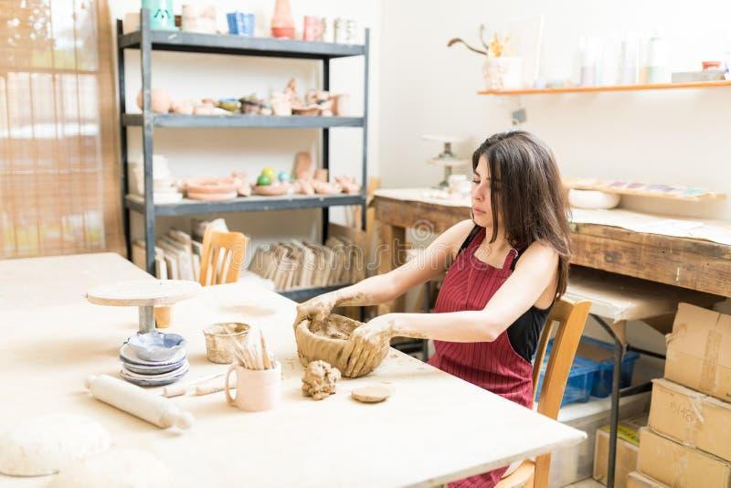 Kvinnlig hantverkare som gjuter Clay In Pottery Workshop arkivfoton