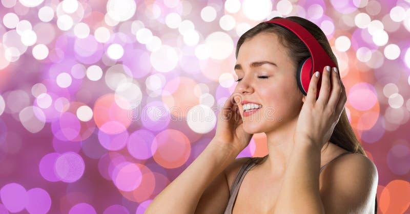 Kvinnlig hipster som lyssnar till musik på hörlurar mot bokeh royaltyfri foto
