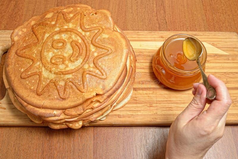 Kvinnlig honung för handtagandeskeden från den glass kruset och sätter på pannkakor arkivfoto