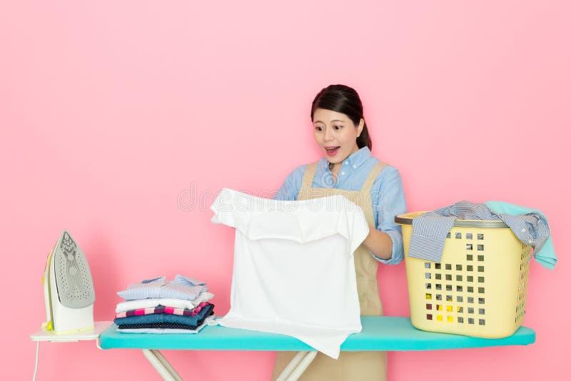 Kvinnlig houseworker som ser vita kläder arkivfoto
