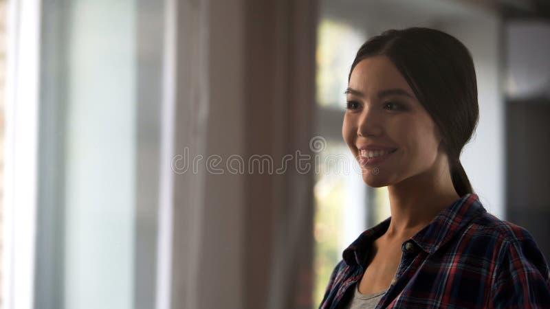 Kvinnlig hushållerska som ser tillfredsställd på rumfönstret, når att ha gjort ren, hygien royaltyfri fotografi
