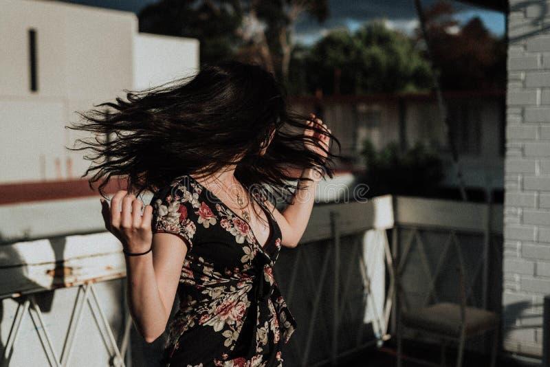 Kvinnlig i en gullig sommarklänningdans på taket arkivfoton