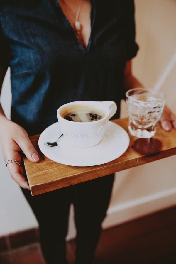 Kvinnlig i en låg klippt skjorta som rymmer ett trämagasin med kaffe och kolsyrat vatten på det royaltyfria bilder