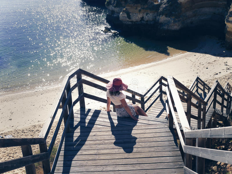 kvinnlig i en röd hatt på trämomenten av trappan på stranden i Portugal arkivbilder