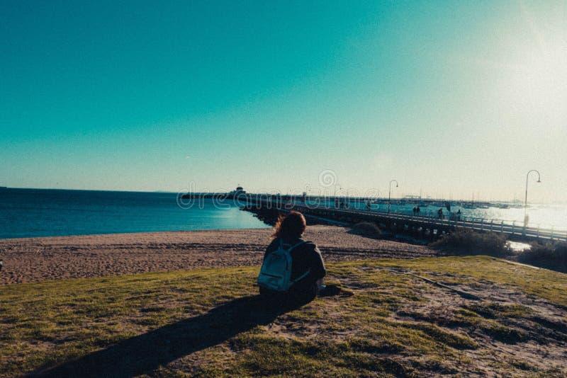 Kvinnlig i en ryggsäck som sitter på kusten av havet nära en pir fotografering för bildbyråer