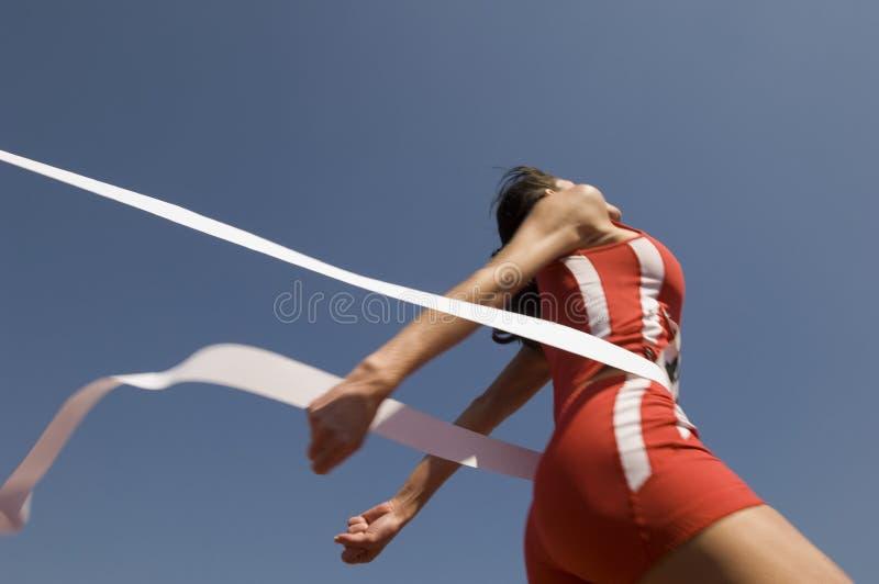Kvinnlig idrottsman nen Crossing Finish Line mot blå himmel arkivfoto