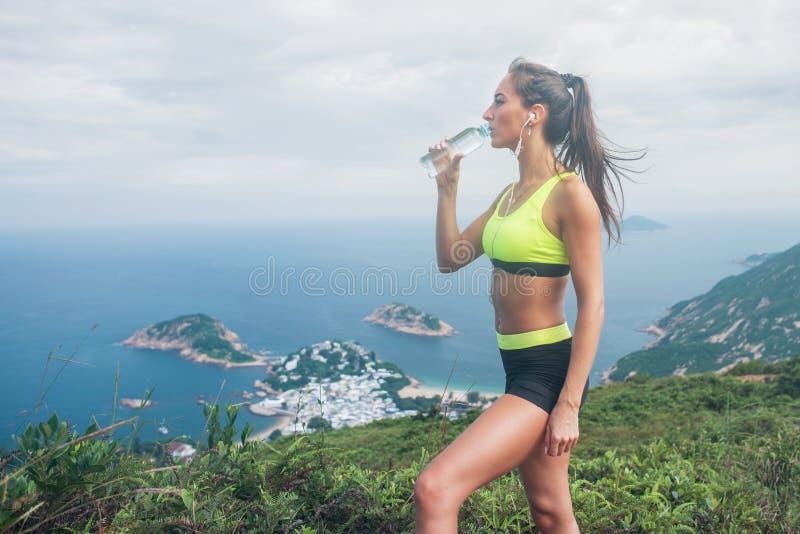 Kvinnlig idrottsman nen, dricksvatten och att lyssna till musik i hörlurar, vila och återställande från spring eller att öva arkivfoton
