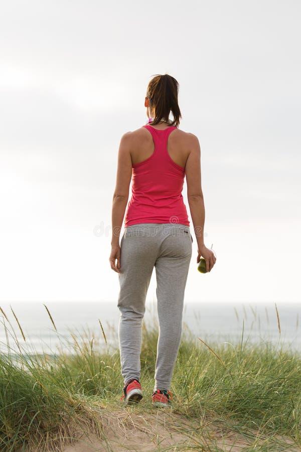 Kvinnlig idrottsman nen för kondition som ser havet royaltyfri fotografi