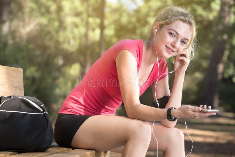 Kvinnlig idrottsman nen med hörlurar som sitter på bänk royaltyfri foto