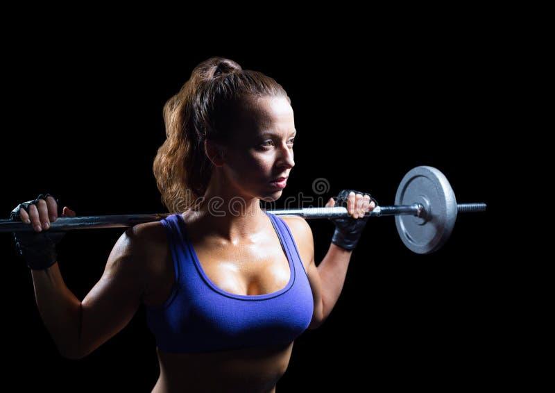 Kvinnlig idrottsman nen med vikter som ser upp mot svart bakgrund arkivfoto