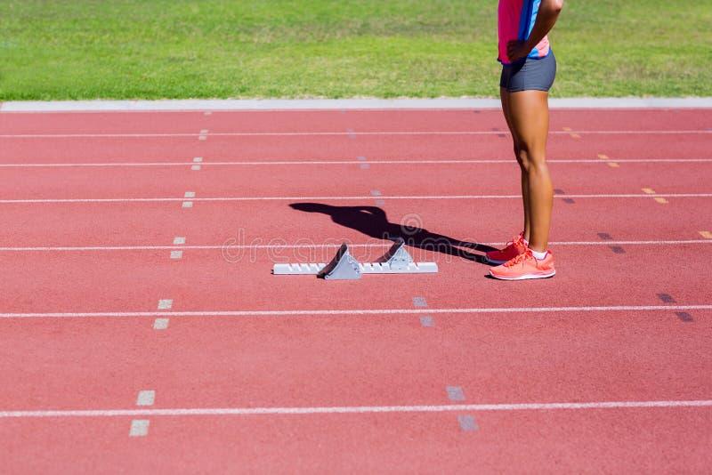 Kvinnlig idrottsman nen som är klar att köra på rinnande spår arkivbilder