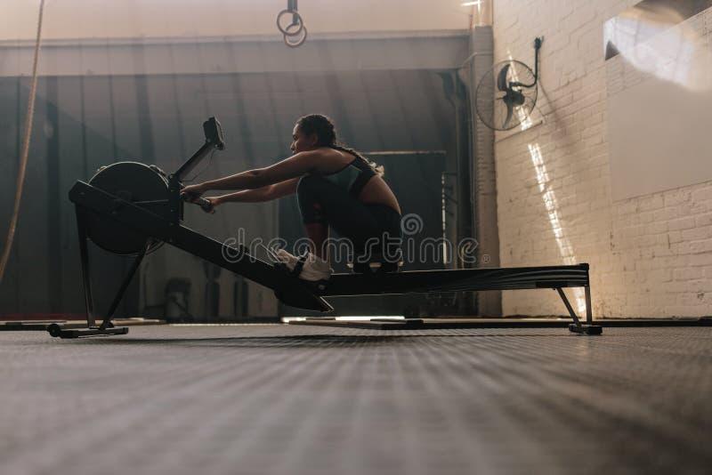 Kvinnlig idrottsman nen som använder roddmaskinen royaltyfri fotografi