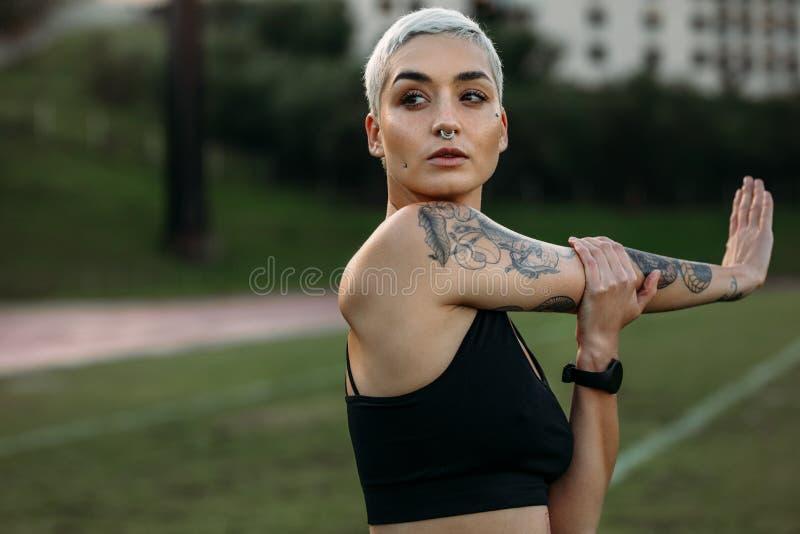 Kvinnlig idrottsman nen som gör genomköraren som sträcker hennes arm arkivbilder