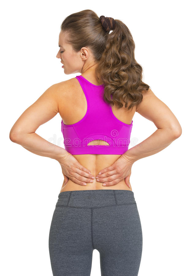 Kvinnlig idrottsman nen som har ryggvärk arkivfoton