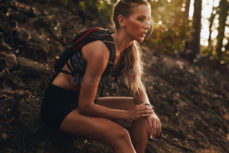 Kvinnlig idrottsman nen som kopplar av efter en slingakörning royaltyfri foto