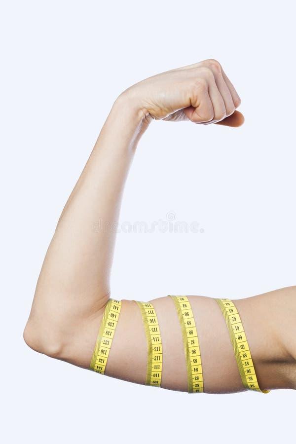 Kvinnlig idrottsman nen som sträcker biceps royaltyfria foton