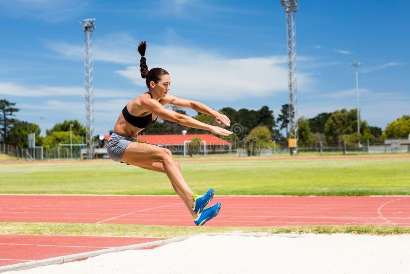 Kvinnlig idrottsman nen som utför ett längdhopp royaltyfria bilder