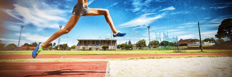 Kvinnlig idrottsman nen som utför ett längdhopp arkivfoton