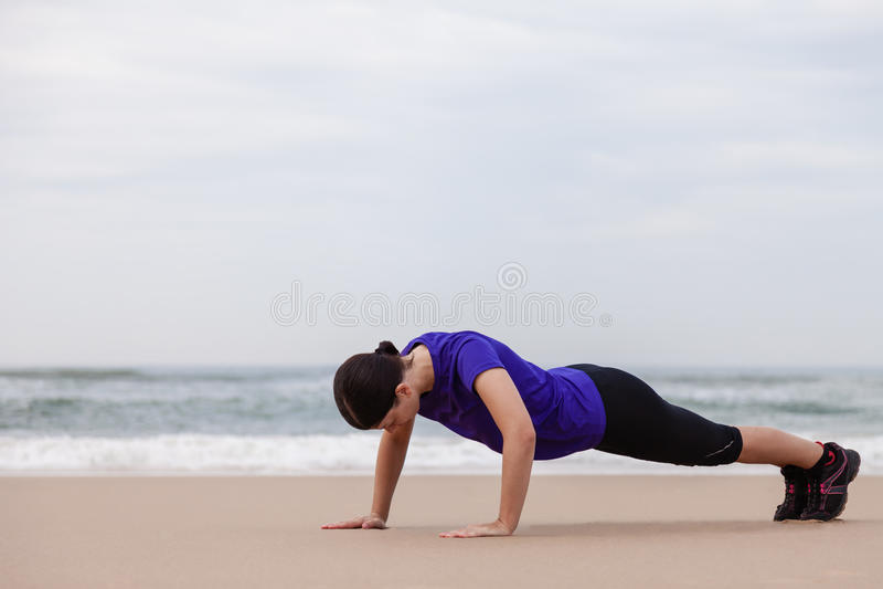 Kvinnlig idrottsman nen som utför push-UPS på stranden arkivfoto