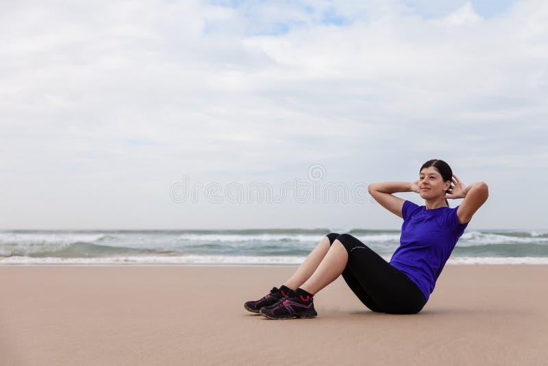 Kvinnlig idrottsman nen som utför situpsen på stranden fotografering för bildbyråer