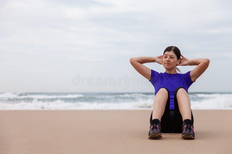 Kvinnlig idrottsman nen som utför situpsen på stranden royaltyfri bild