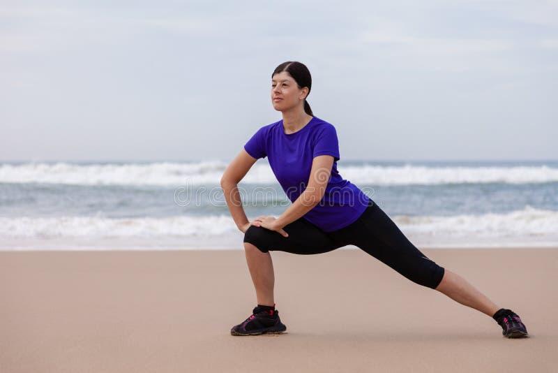 Kvinnlig idrottsman nen som värmer och sträcker benen, innan att köra på stranden upp arkivfoton