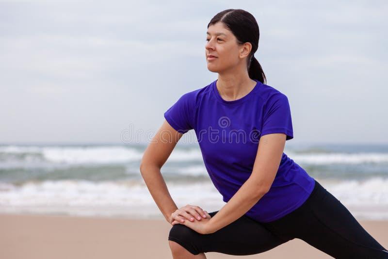 Kvinnlig idrottsman nen som värmer och sträcker benen, innan att köra på stranden upp royaltyfria bilder